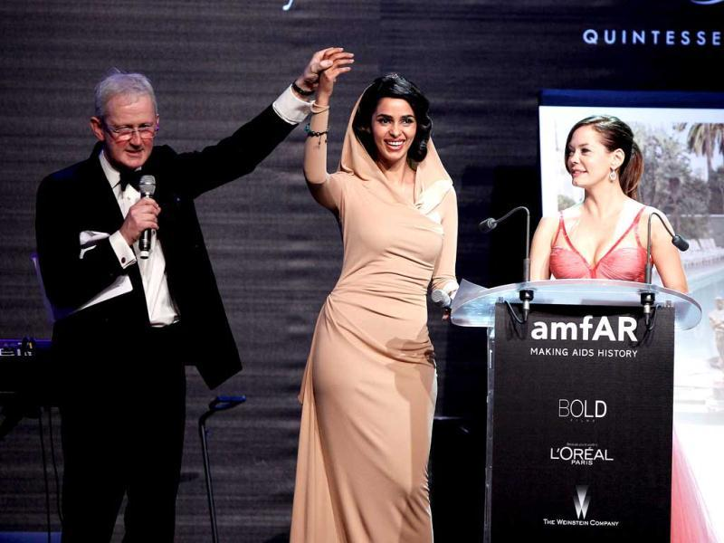 Holier than thou? Actresses Mallika Sherawat and Rose McGowan speak onstage during the 2012 amfAR's Cinema Against AIDS during the 65th Annual Cannes Film Festival.