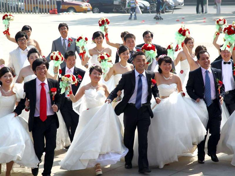 A group of 18 Chinese couples taking part in a mass wedding ceremony in Beijing. China's wedding market, estimated to be worth nearly $60 billion, where 10 million weddings take place annually -- five times as many as in the US, is by far the world's largest. AFP Photo