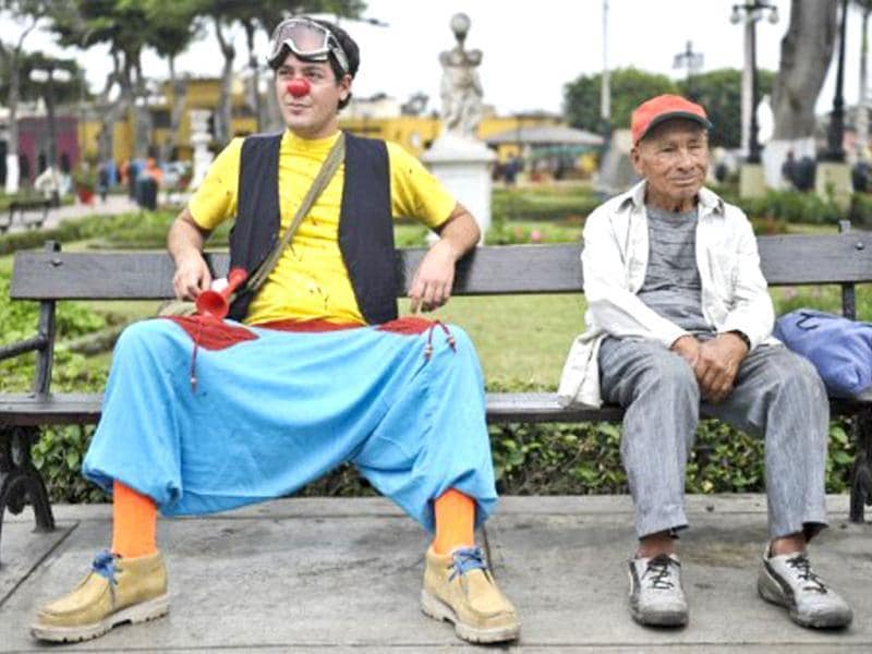 A clown sits on a park bench next to an elderly man, as hundreds of clowns demonstrate in the streets of Lima to demand the Peruvian Congress to create a