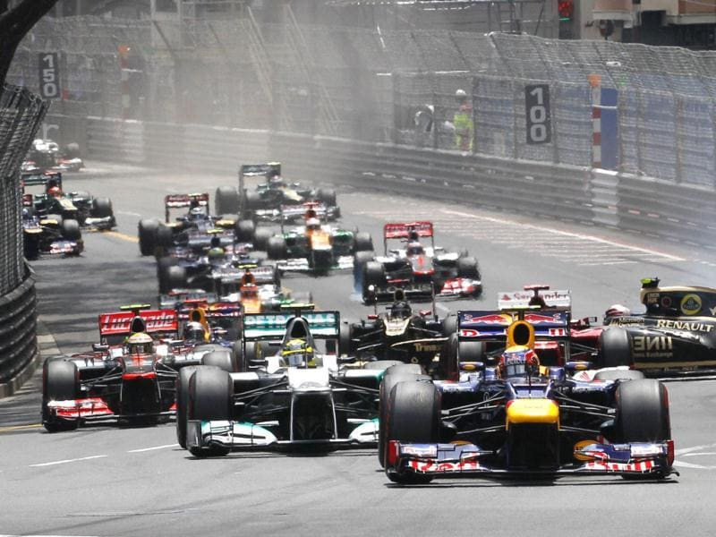 Red Bull driver Mark Webber of Australia leads the field after the start as Lotus driver Romain Grosjean of France crashes, in background, during the first lap of the Formula One Grand Prix, at the Monaco racetrack, in Monaco. (AP Photo/Luca Bruno)