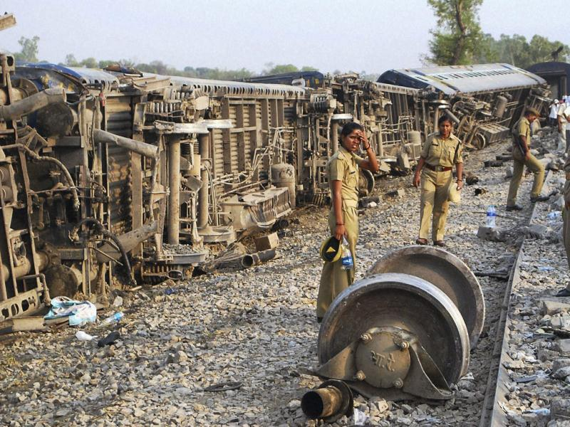 Policemen guard near the site of accident after Doon Express, on its way from Howrah to Dehradun, derailed near Koridia village about 35 km from Jaunpur in Uttar Pradesh. PTI Photo