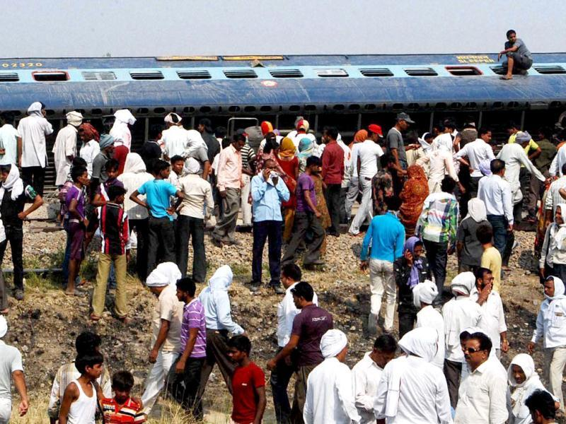People gather near the site of accident after Doon Express, on its way from Howrah to Dehradun, derailed near Koridia village about 35 km from Jaunpur in Uttar Pradesh. PTI Photo