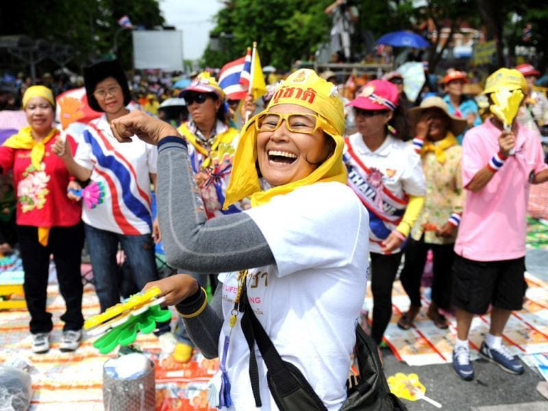A member of the royalist Yellow Shirts dances during a protest against a proposed reconciliation debate, outside the parliament in Bangkok. AFP/Aaron Tam