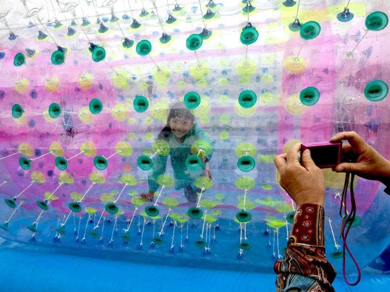A woman takes a picture of her granddaughter playing inside a balloon float on water at the Chaoyang park during International Children's Day in Beijing. AP/Andy Wong