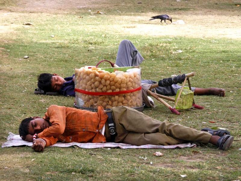A commuter and a street vendor sleep under a tree to beat the heat, in New Delhi. Temperatures in the capital soared to 45 degrees Celsius for the past two days. (AP Photo)