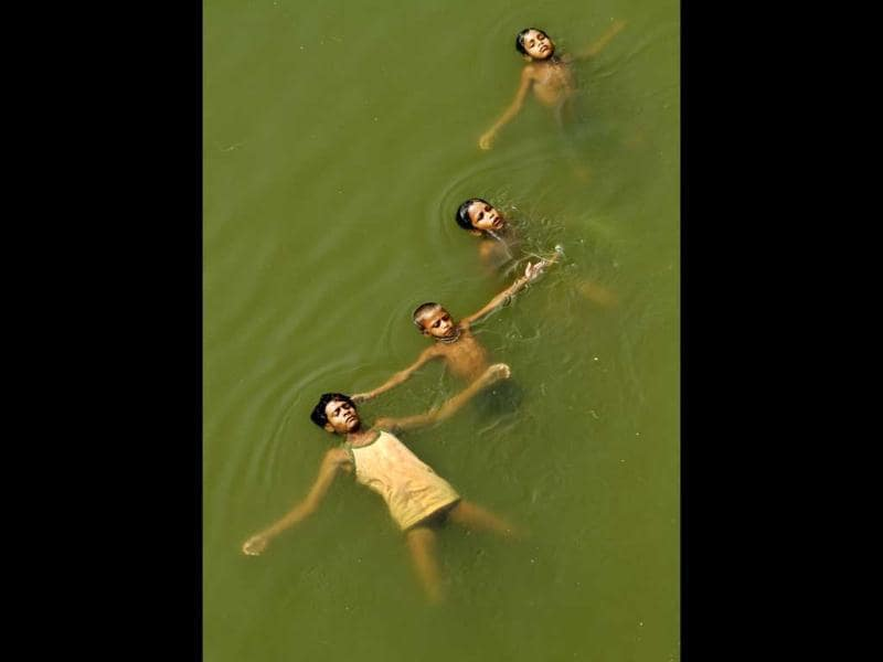 Young boys submerge themselves in water to cool off on a hot summer day in Jaunpur. The weather in northern India has been extremely hot in recent days with temperatures reaching as high as 45 degrees Celsius. (AP Photo)