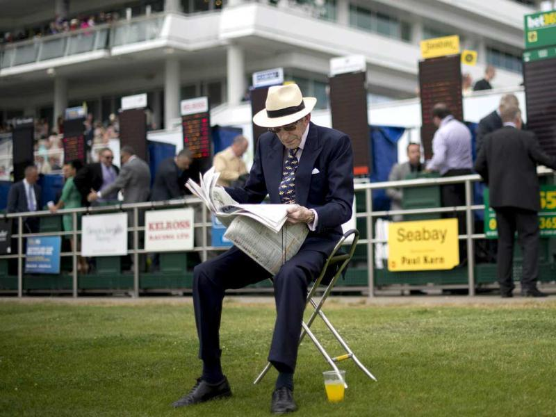 A racegoer reads the form guide during Ladies' Day, the first day of the Epsom Derby horse racing event, at Epsom in Surrey. AFP/Ben Stansall