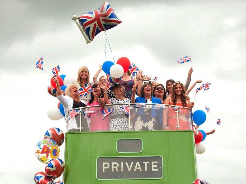 Racegoers on an open-top bus during Investec Ladies' Day of the Investec Derby Festival at Epsom Racecourse, Epson. AP/Dominic Lipinski