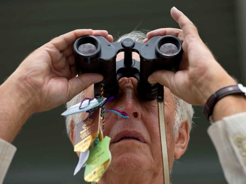 A racegoer looks through binoculars during Ladies' Day, the first day of the Epsom Derby horse racing event, at Epsom in Surrey. AFP/Ben Stansall