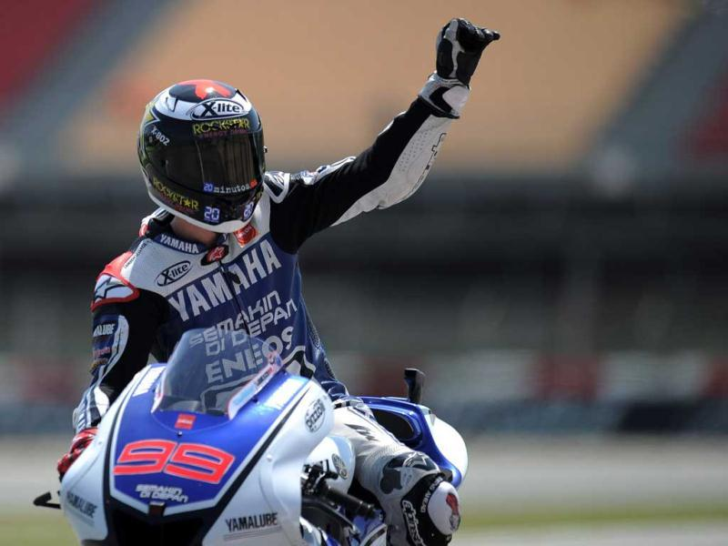 Yamaha Factory Racing's Spanish Jorge Lorenzo waves to supporters at the Catalunya racetrack in Montmelo, near Barcelona, after the MotoGP second training session of the Catalunya Moto GP. AFP Photo/Lluis Gene