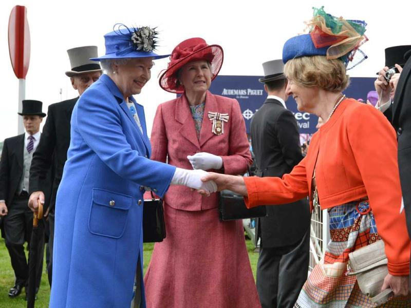 Britain's Queen Elizabeth II (R) shakes hands with a racegoer as Lord Lieutenant of Surrey Sarah Goad (C) follows behind as she arrives on Derby Day, the second day of the Epsom Derby horse racing festival, at Epsom in Surrey, the first official day of Britain's Queen Elizabeth II's Diamond Jubilee celebrations. AFP/Ben Stansall