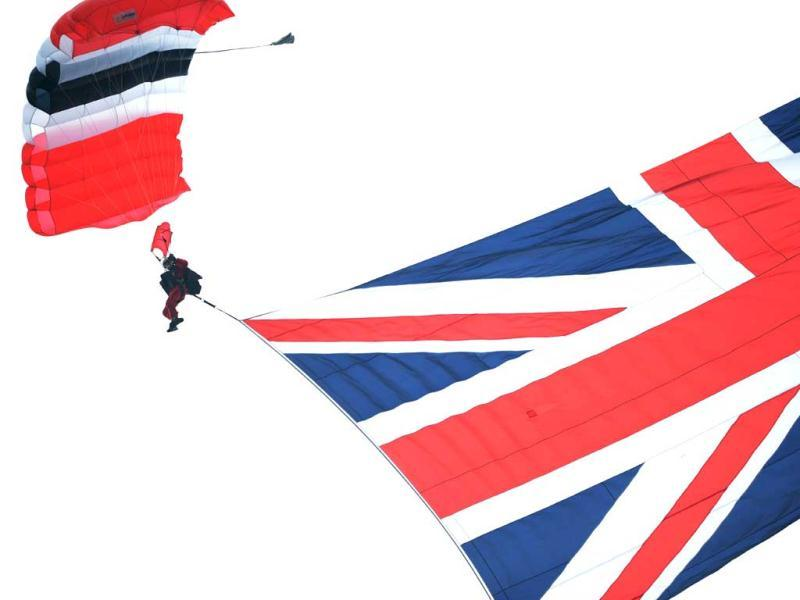 A member of the Red Devils aerobatics group parachutes onto the racecourse with a big Union Flag on Derby Day, the second day of the Epsom Derby horse racing festival, at Epsom in Surrey, southern Englandm, the first official day of Britain's Queen Elizabeth II's Diamond Jubilee celebrations. AFP/Adrian Dennis