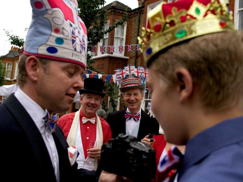 Residents wearing flags and crowns on their heads take part in a street party organised by residents of Battersea in south London as Britain celebrates Queen Elizabeth II's Diamond Jubilee. AFP/Andrew Cowi