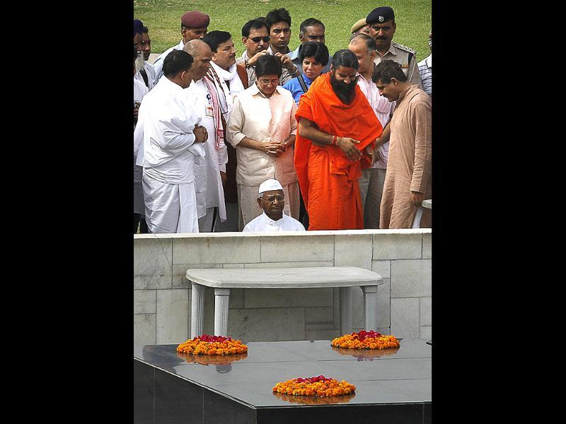 Anna Hazare and yoga guru Baba Ramdev offer tributes at the Mahatma Gandhi memorial, along with supporters, before starting their day-long fast, in New Delhi. AP/Manish Swarup