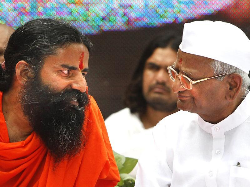Anna Hazare (R) talks to Baba Ramdev during a day long fast near Parliament house in New Delhi. AP/Mustafa Quraishi