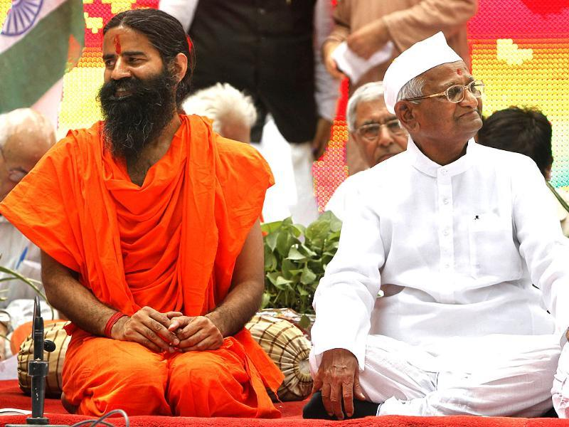Anna Hazare (R) and Baba Ramdev listen to a speaker during a day-long fast near Parliament house in New Delhi. AP/Mustafa Quraishi