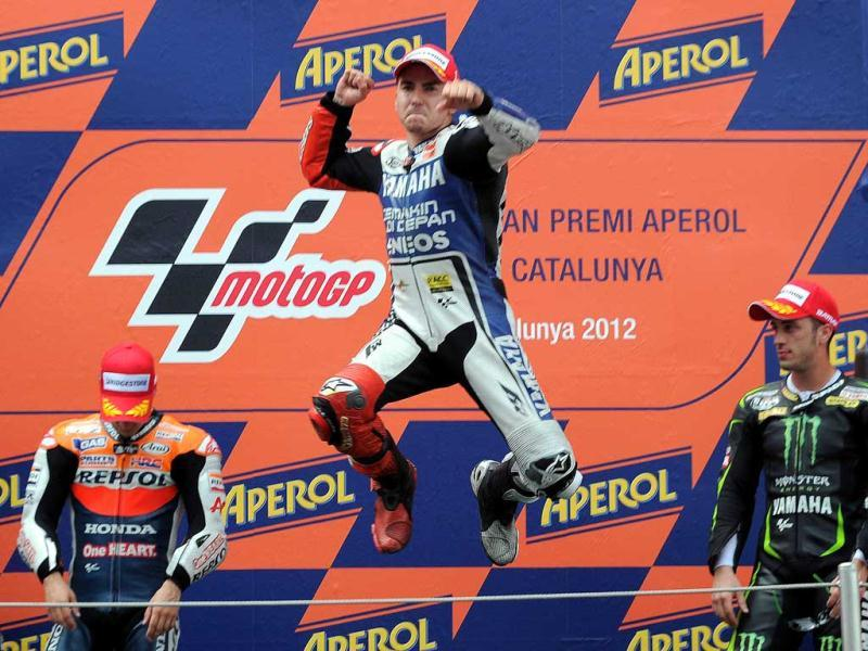 Yamaha Factory Racing's Spanish Jorge Lorenzo (C) celebrates on the podium after winning the MotoGP race of the Catalunya Moto GP at the Catalunya racetrack in Montmelo, near Barcelona. Yamaha Factory Racing's Spanish Jorge Lorenzo won the race ahead of Repsol Honda Team's Spanish Dani Pedrosa (L) and Monster Yamaha Tech 3 Italian Andrea Dovizioso (R). AFP/Lluis Gene