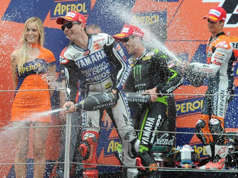 Yamaha Factory Racing's Spanish Jorge Lorenzo (L), Monster Yamaha Tech 3 Italian Andrea Dovizioso (C) and Repsol Honda Team's Spanish Dani Pedrosa (R) celebrate on the podium after the MotoGP race of the Catalunya Moto GP at the Catalunya racetrack in Montmelo, near Barcelona. AFP/Lluis Gene