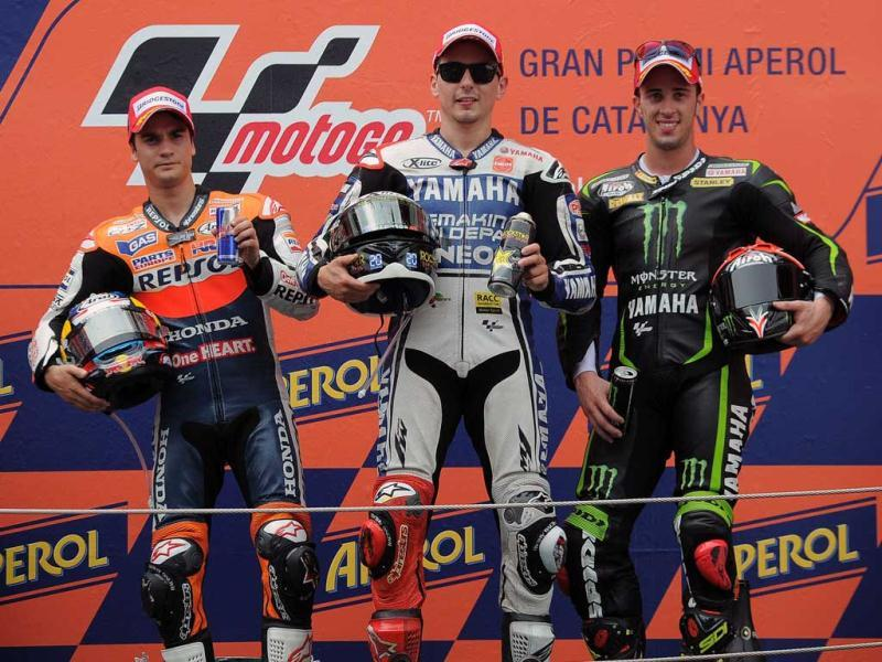 Yamaha Factory Racing's Spanish Jorge Lorenzo (C), Monster Yamaha Tech 3's Italian Andrea Dovizioso (R) and Repsol Honda Team's Spanish Dani Pedrosa celebrate on the podium after the MotoGP race of the Catalunya Moto GP at the Catalunya racetrack in Montmelo, near Barcelona. AFP/Lluis Gene