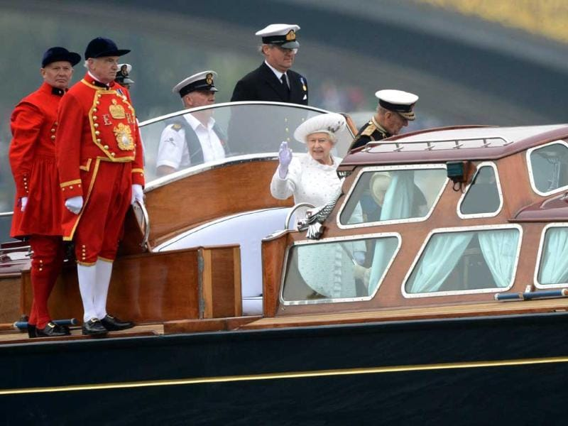 Britain's Queen Elizabeth II (C) and Prince Philip, Duke of Edinburgh (R) ride on the launch to the royal barge 'Spirit of Chartwell' at the start of the Thames Diamond Jubilee Pageant on the River Thames in London on June 3, 2012. Queen Elizabeth II was to sail on a ceremonial barge down the Thames on Sunday at the centre of a 1,000-boat pageant to mark her diamond jubilee, although heavy rain threatened to spoil the party. AFP Photo/Adrian Dennis