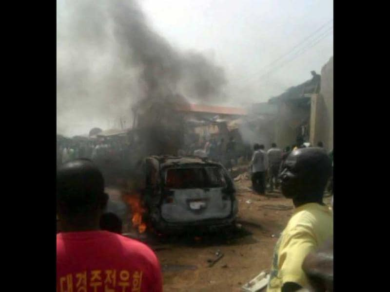 Iju district of Lagos gathering at the site where a Dana company aircraft crashed into a two-storey building on June 3, 2012 in Lagos. More than 150 passengers are feared dead, an aviation official and residents said. Thick smoke rose from the area near the Lagos airport and flames could be seen coming from the building. Residents said the plane had been coming in low, making a loud noise, when it slammed into the residential area.  AFP PHOTO / CKN