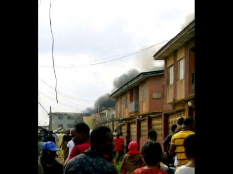 A picuture taken with a photo camera shows residents of the Iju district of Lagos looking at the smoke that rises a few moments after a Dana company aircraft crashed into a two-storey building on June 3, 2012 in Lagos. More than 150 passengers are feared dead, an aviation official and residents said. Thick smoke rose from the area near the Lagos airport and flames could be seen coming from the building. Residents said the plane had been coming in low, making a loud noise, when it slammed into the residential area.  AFP PHOTO / CKN