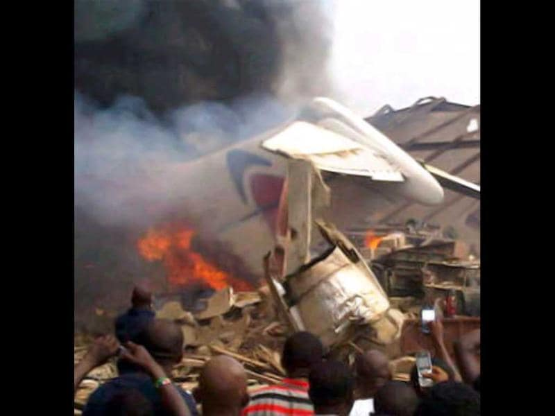 A picture taken with a photo camera shows residents of the Iju district of Lagos gathering at the site where a Dana company aircraft crashed into a two-storey building on June 3, 2012 in Lagos. AFP PHOTO / CKN