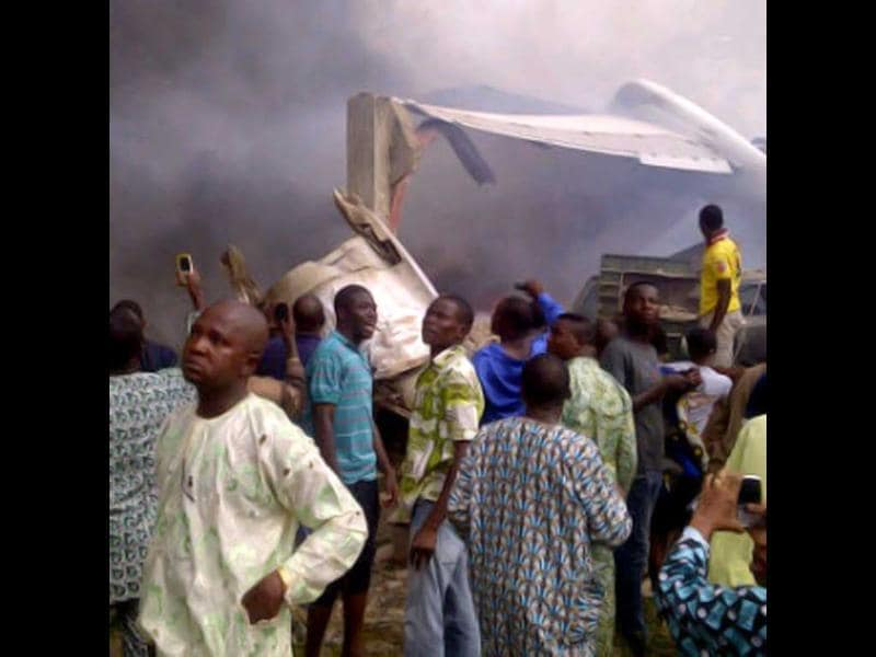 A picture taken with a photo camera shows residents of the Iju district of Lagos gathering at the site where a Dana company aircraft crashed into a two-storey building on June 3, 2012 in Lagos. More than 150 passengers are feared dead, an aviation official and residents said. Thick smoke rose from the area near the Lagos airport and flames could be seen coming from the building. Residents said the plane had been coming in low, making a loud noise, when it slammed into the residential area.  AFP PHOTO / CKN