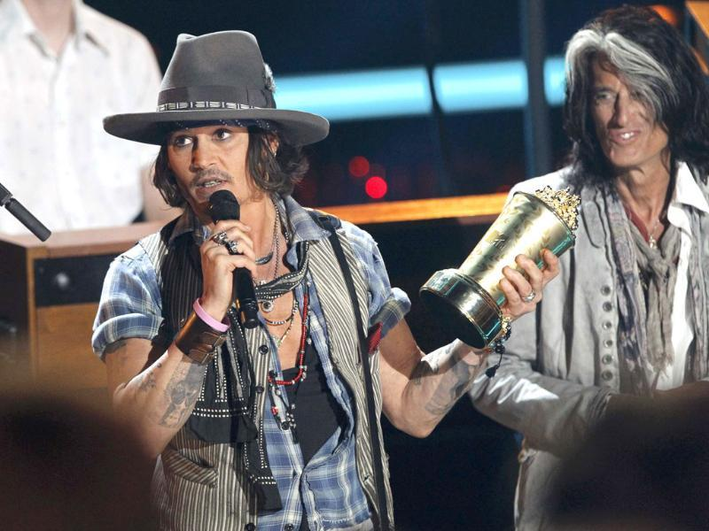 Johnny Depp (L) accepts the MTV Generation Award as presenter Joe Perry of Aerosmith watches on at the 2012 MTV Movie Awards in Los Angeles. Reuters/Mario Anzuoni
