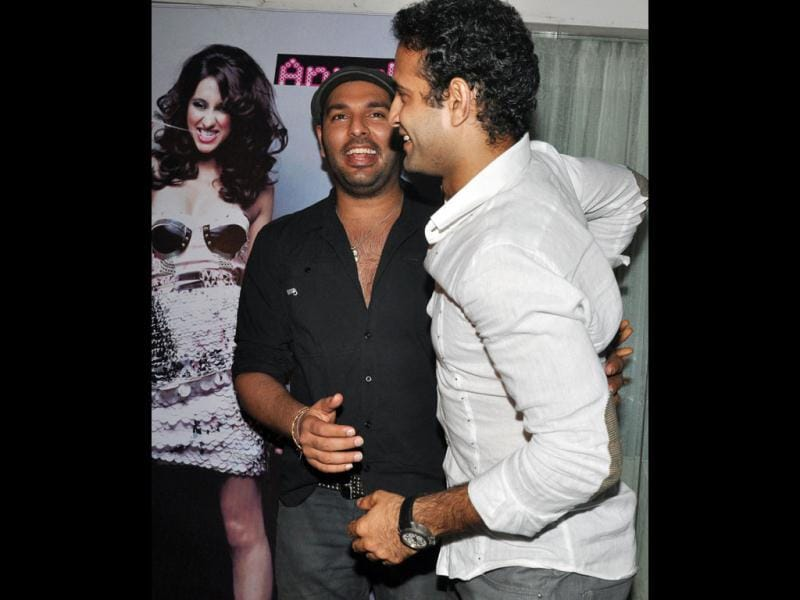Yuvraj Singh and Irfan Pathan pose in front of a poster of Anusha Dandekar.
