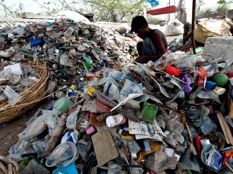 A rag-picker sorts through plastic bottles and polythene bags near a garbage land fill on World Environment Day in New Delhi. AFP/Prakash Singh