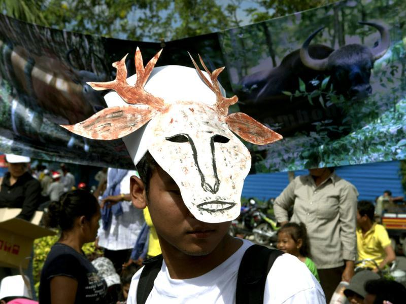 A Cambodian environmental activist wears a mask symbolizing a wild animal as he stands in front of a banner during a rally to mark World Environment Day in Phnom Penh, Cambodia. AP/Heng Sinith