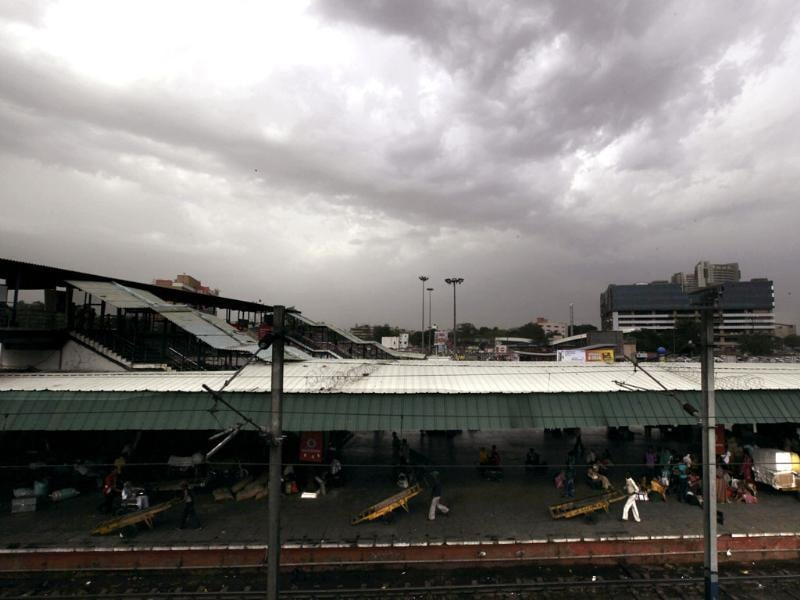 Railway workers push their carts through a platform as rain clouds hover over in New Delhi. (AP Photo/ Manish Swarup)