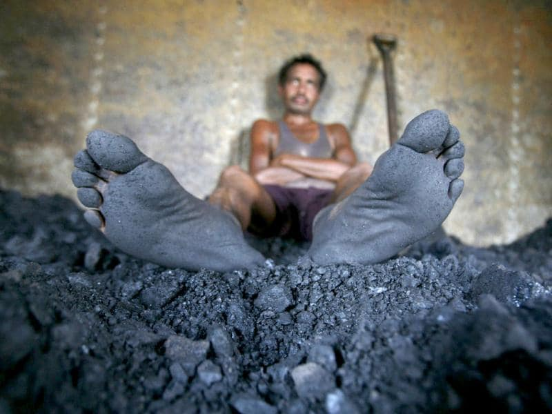 A labourer rests inside the wagon of a coal train as he takes a break from shovelling coal at a coal yard on the outskirts of Jammu. Reuters/Mukesh Gupta, File