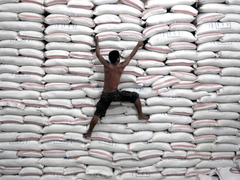 A worker climbs on a pile of rice stock inside a warehouse of the government National Food Authority (NFA) in Bicutan, south of Manila. Reuters/Romeo Ranoco, File