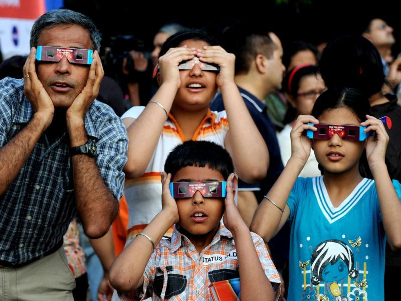 A family in New Delhi uses special glasses and filters to observe Venus as it passes in front of the Sun. Astronomers around the world trained their telescopes on the skies to watch Venus pass in front of the Sun, a once-in-a-lifetime event that will not be seen for another 105 years. AFP/Sajjad Hussain