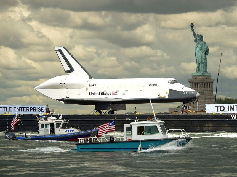 The US space shuttle Enterprise atop a barge passes the Statue of Liberty in New York on its way to the Intrepid Sea, Air and Space Museum where it will be permanently displayed. AFP Photo/NASA