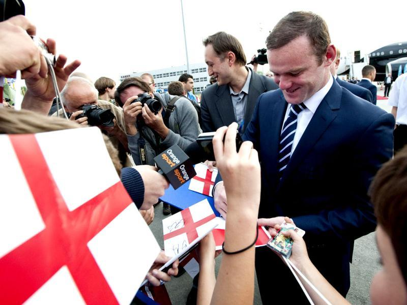 National football team of England forward Wayne Rooney signs autographs for children as he arrives at Krakow Airport ahead of the Euro 2012 football championships which will kick-off on June 8 in Warsaw. AFP/Bartosz Siedlik