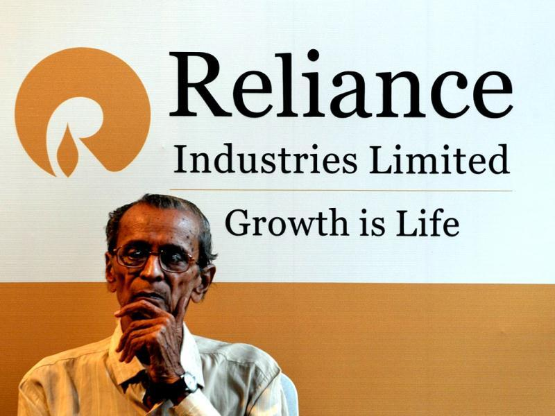 A shareholder sits beside a Reliance Industries Limited poster during the company's annual general meeting in Mumbai. AFP/Indranil