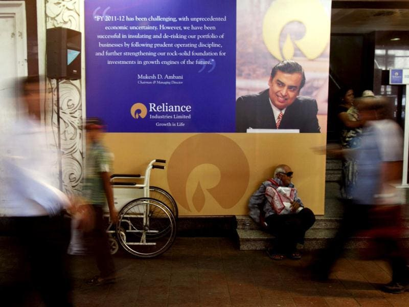 A shareholder sits beneath a photograph of Reliance Industries chairman Mukesh Ambani as he waits to attend the company's annual general meeting in Mumbai. AP/Rafiq Maqbool