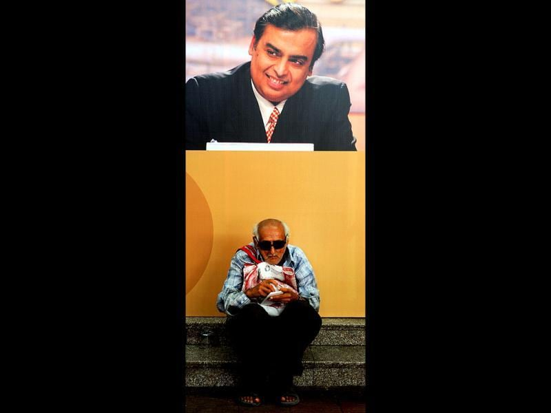 A shareholder sits underneath a poster bearing the portrait of Reliance Industries Limited chairman Mukesh Ambani during the company's annual general meeting in Mumbai. AFP/Indranil