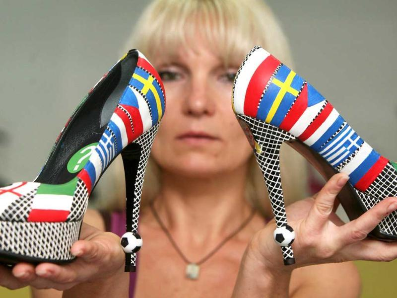 A woman shows shoes designed by Igor Zaytsev decorated with flags she sells at her shop ahead of the Euro 2012 football championships in Donetsk. AFP/Alexander Khudoteply