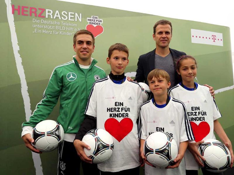 Germany's national soccer player Philipp Lahm (L) and manager Oliver Bierhoff pose for photographers before a news conference ahead of the Euro 2012 in Gdansk. Reuters/Thomas Bohlen