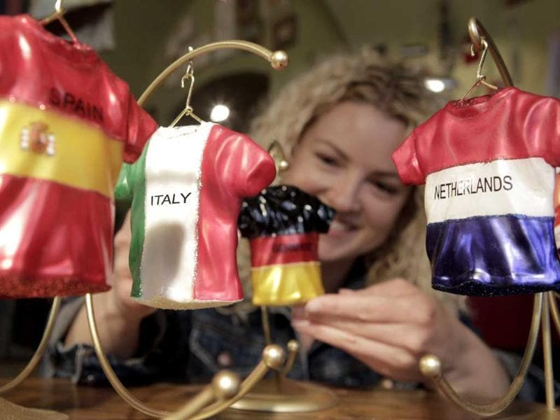 Tiffany Beveridge from Philadelphia, takes a look at handmade Polish porcelain decorations of soccer jerseys from Spain, Italy, Germany and the Netherlands during the Euro 2012 soccer championships in a shop in Warsaw, Poland. AP/Gero Breloer