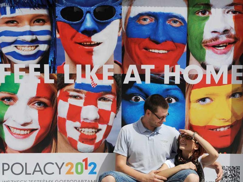 A couple sit in front of a Euro 2012 football championships sign reading 'Feel like at home' in Wroclaw, on the eve of the opening match in Warsaw. AFP/Daniel Mihailescu