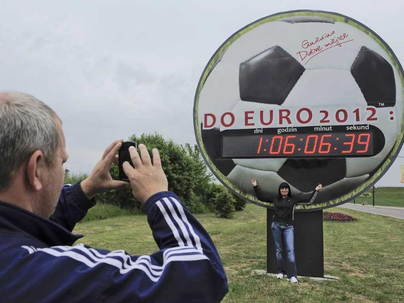 A soccer enthusiast takes a photograph of a woman as she poses in front a giant clock displaying the countdown to the Euro 2012 soccer championship, in Gniewino, Poland. AP/Alvaro Barrientos