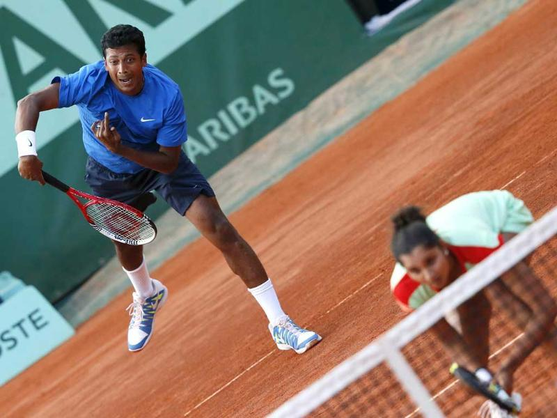 Mahesh Bhupathi (L) serves near Sania Mirza as they play against Poland's Klaudia Jans-Ignacik and Mexico's Santiago Gonzalez during their mixed doubles final match of the French Open tennis tournament at the Roland Garros stadium in Paris. AFP/Kenzo Tribouillard