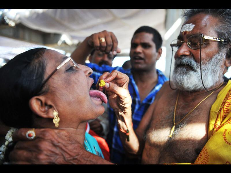 Bathini Harinath Goud administers fish medicine to a patient at the Katedan stadium in Hyderabad. AFP Photo/Noah Seelam