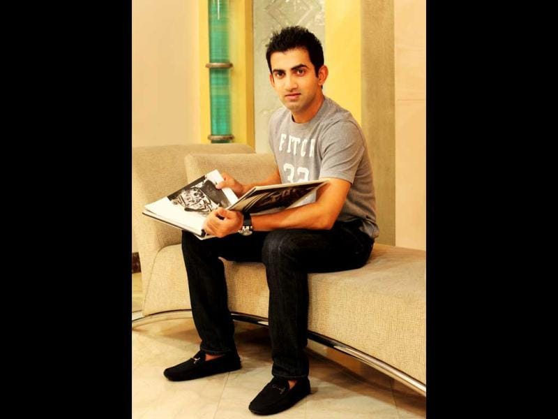 Gambhir browsing through a coffee table book on Mother Teresa (HT Photo: Ajay Aggarwal)