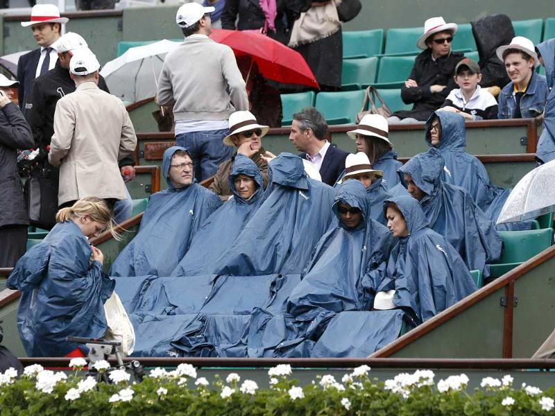 Spectators protect themselves from rain as Rafael Nadal and David Ferrer play during their semifinal tennis match of the French Open tournament at the Roland Garros stadium in Paris. AFP/Thomas Coex